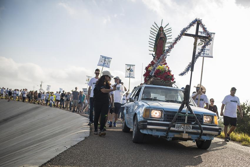The Save the Mission! Save the River! Resist the Wall! procession atop the levee on the way to La Lomita Mission in Mission,…