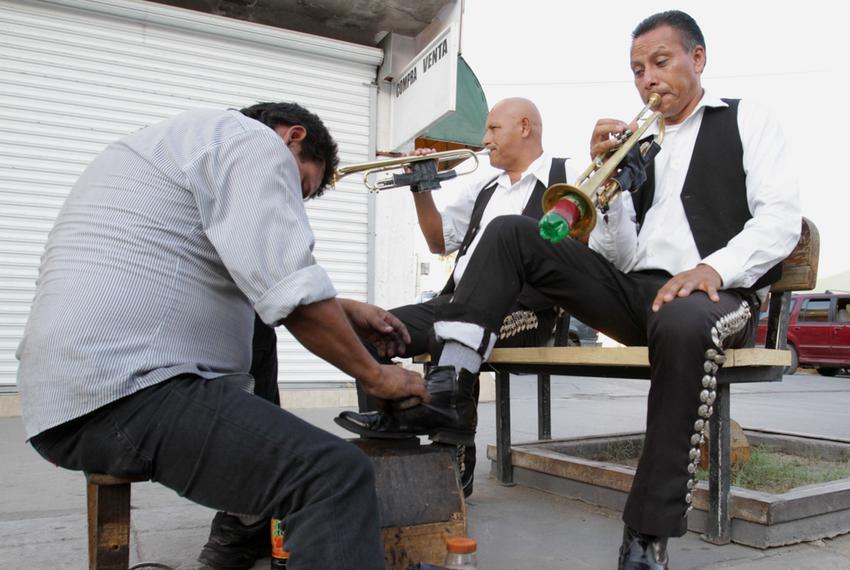 Ignacio Villa, left, and Arturo Ibarra, right, of the mariachi group Los Gavilanes receive shoe shines on Avenida Juárez in …