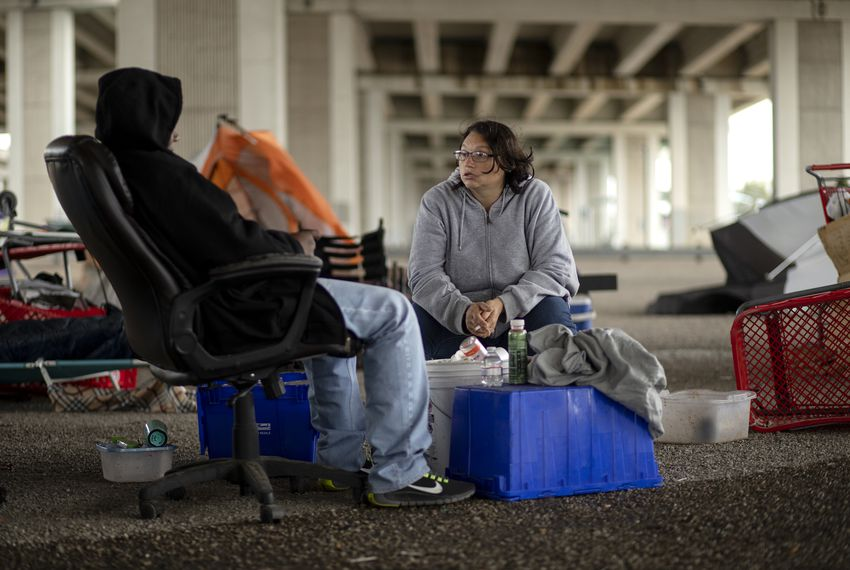 Crystal Brimm is experiencing homeless and is currently living under Ben White Boulevard and Lamar Avenue. She discusses with her partner the possibility of moving to a 5 acre homeless camp recently created by Gov. Greg Abbott. Nov. 7, 2019.