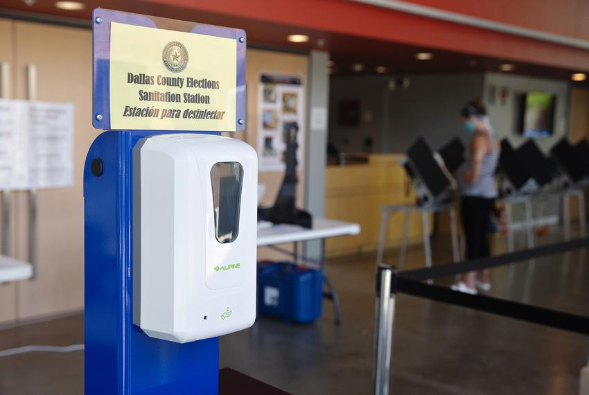 A sanitation station is positioned at the entrance of a polling site at Booker T. Washington High School in Dallas on July 1…