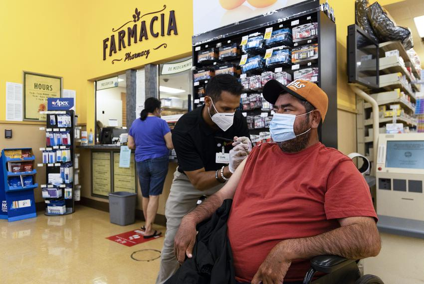 Pharmacist Cody Frausto gives Alfredo Pacheco his does of the Johnson & Johnson COVID-19 vaccine at Amigos Pharmacy in Amari…