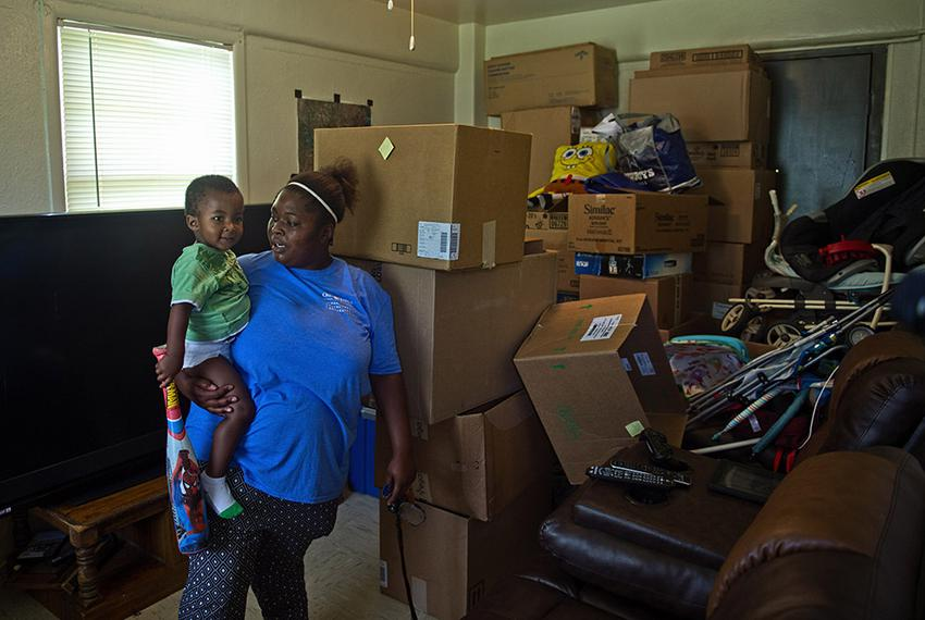 D.N. Leathers Public Housing Complex resident Jasmine Mosley holds her son De' Monei Traylor, 2 in their apartment on Sept...