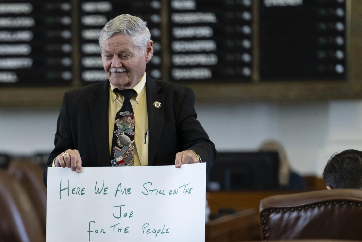"""Rep. Charles """"Doc"""" Anderson, R-Waco, holds a sign that reads, """"Here we are still on the job for the people,"""" on the House floor on July 14, 2021."""