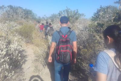 Nicaraguan migrant Grisber Calero, carrying a red and black backback, walks along a trail near the highway between Monterrey and Reynosa, Mexico, in order to avoid a law enforcement checkpoint in August 2018.