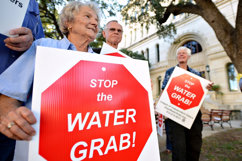 Lee County resident Hilde Sides protests the Vista Ridge Water Supply Project with other Lee and Bastrop County residents outside the San Antonio City Council public hearing on the project on Oct. 8, 2014.