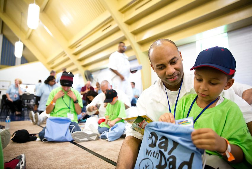 A boy opens a gift bag from his father, an inmate at a maximum-security facility south of Houston during a 2016 gathering for prisoners and their children called Day with Dad. A new study looked at the impact incarceration has on prisoners' families.
