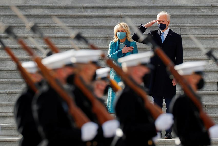 U.S. President Joe Biden salutes as first lady Jill Biden puts her hand over her heart during the pass in review after the i…