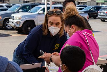 Marisa Gonzales helps a woman register for a COVID-19 vaccination appointment at an event in Irving on March 19, 2021.
