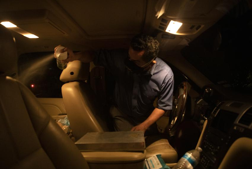 Juan Lopez sprays disinfectant after placing a body in the interior of his vehicle in McAllen. Lopez picks up the bodies of …