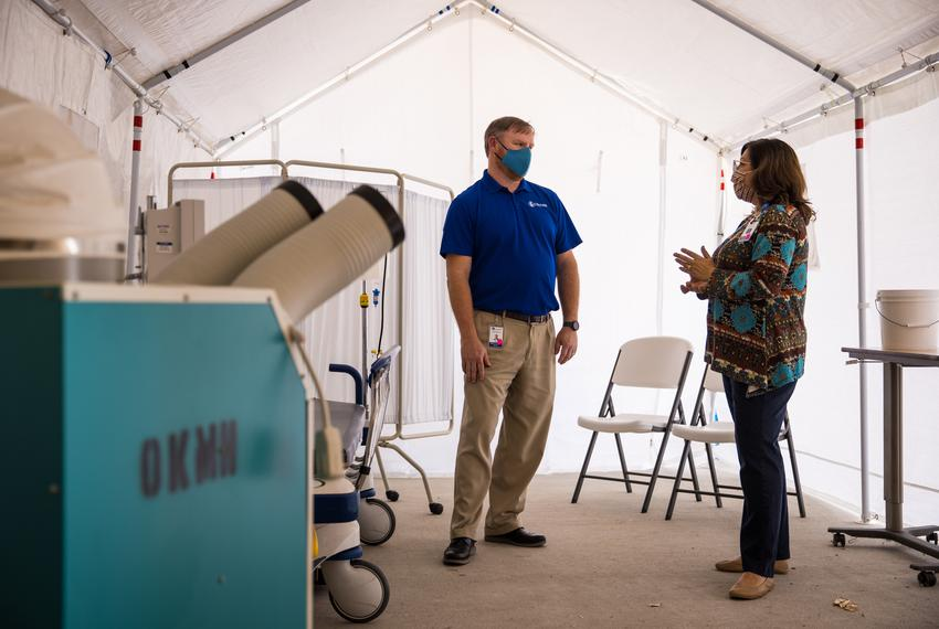 David Lee, Chief Executive Officer, speaks with Barbara James inside a tent set aside for triaging COVID-19 patients located…