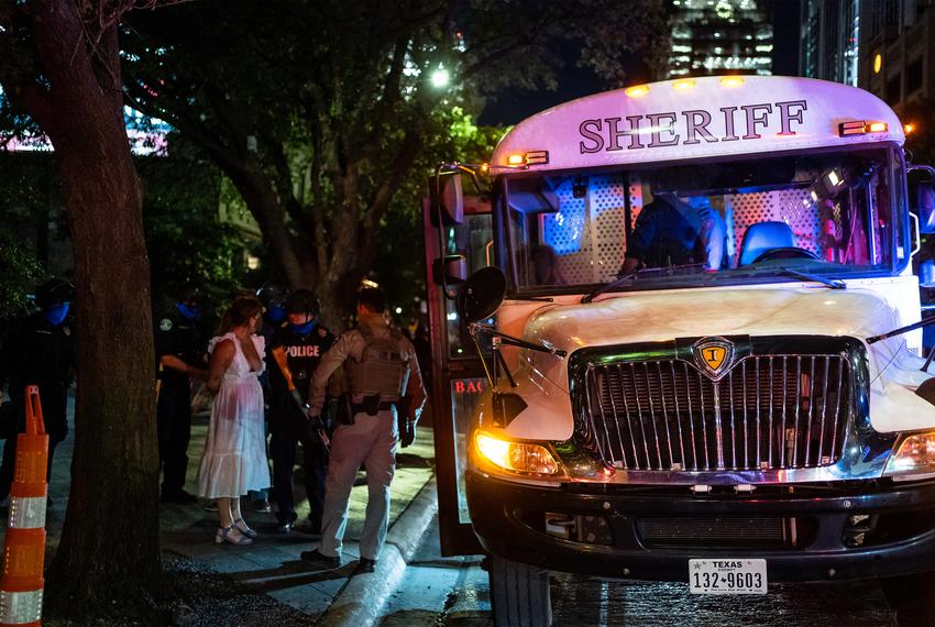 Police load arrested protesters into a Travis County Sheriff's Department bus. Several protestors were arrested after clas...