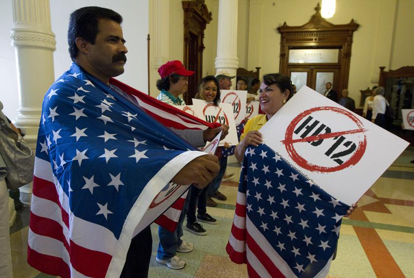Protesters with signs and American flags line the hallway outside the Senate chamber on sanctuary cities bill HB12 on May 25…