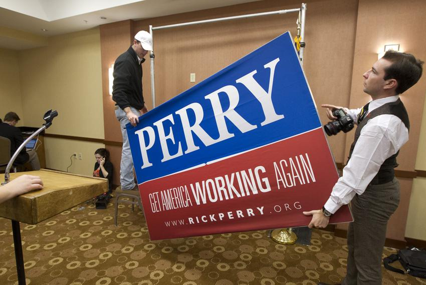 Perry campaign workers take down the final sign of Perry's presidential campaign at the Hyatt Place Hotel where he announced…