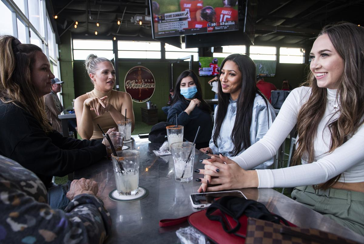 Friends have drinks at Little Woodrow's during the Texas Tech home coming game against West Virginia on Saturday, Oct. 24, 2020, in Lubbock.