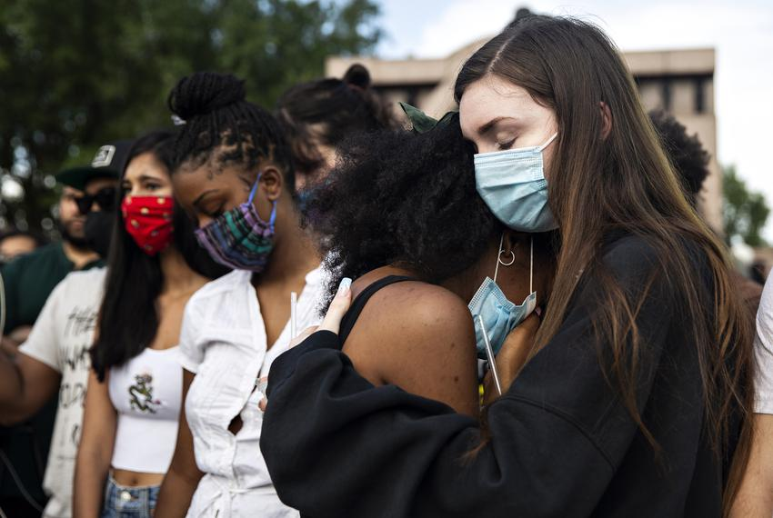 From right, Taylor Putnam comforts her friend Veronica Holmes at a vigil honoring those who's lives were lost to police shoo…