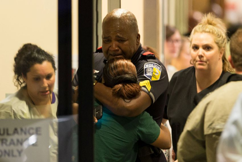 A Dallas Area Rapid Transit police officer receives comfort at the Baylor University Hospital emergency room entrance following a sniper attack that targeted law enforcement.