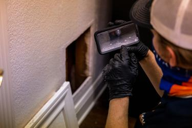 Zachary Shockency, a technician with Radiant Plumbing, uses his phone to take a video of a leaky pipe that caused flooding during last week's winter storm at a home in West Austin on Feb. 24, 2021.
