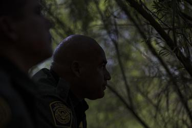 Border Patrol Agents José Perales and Isaac Villegas peer out along the Rio Grande riverbank while searching for a group of five people reported to have crossed the river in a raft from Ciudad Miguel Alemán.