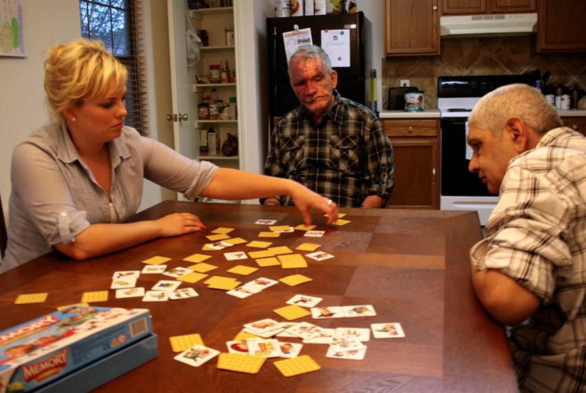 Health care assistant Crystal Kreig plays a card game with Steve Parker (center) and Eulalio Alvarada (right) at a group hom…