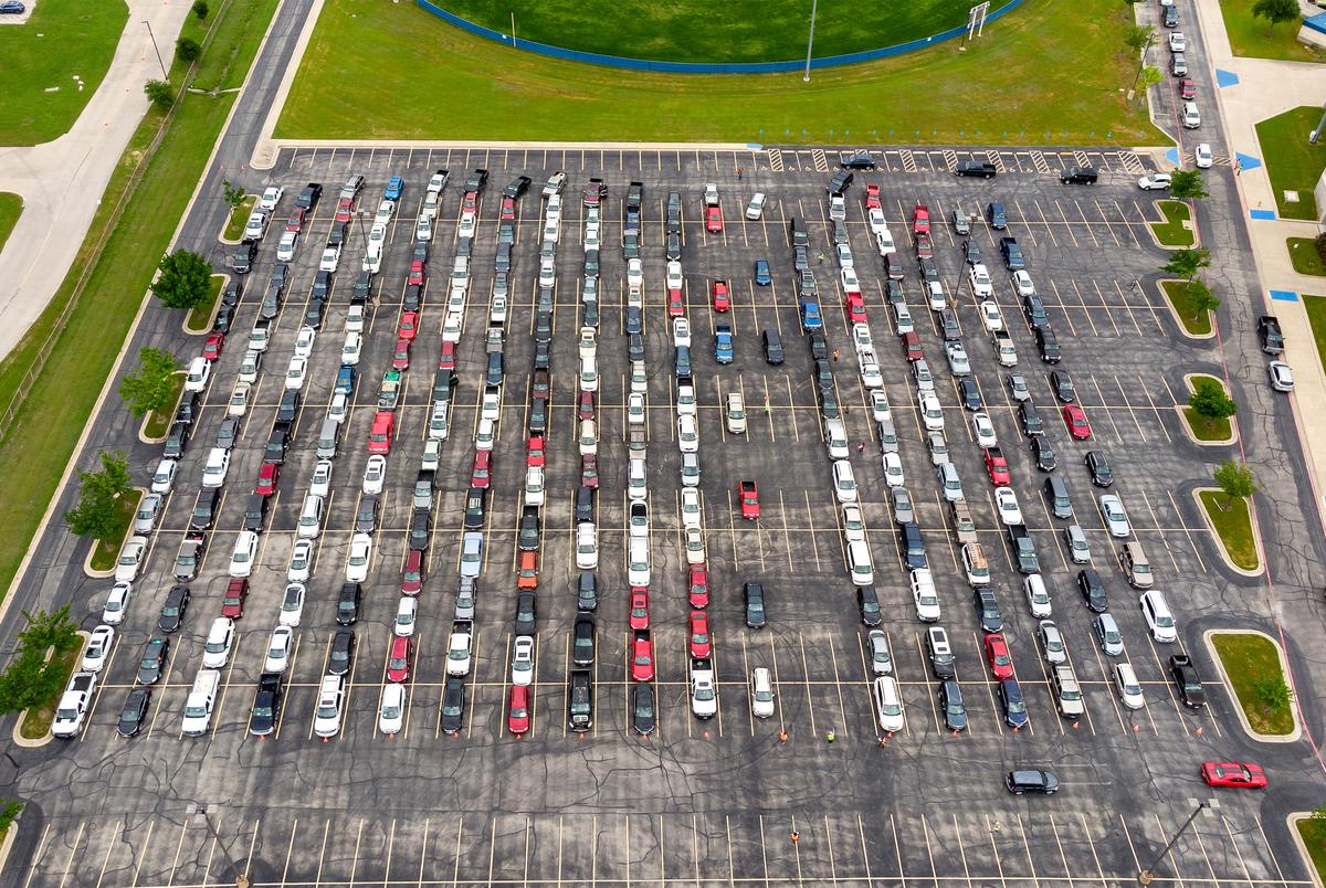 The parking lot of the Waco ISD Stadium is full of cars waiting to receive disaster relief food boxes from the Central Texas Food Bank on April 14, 2020.