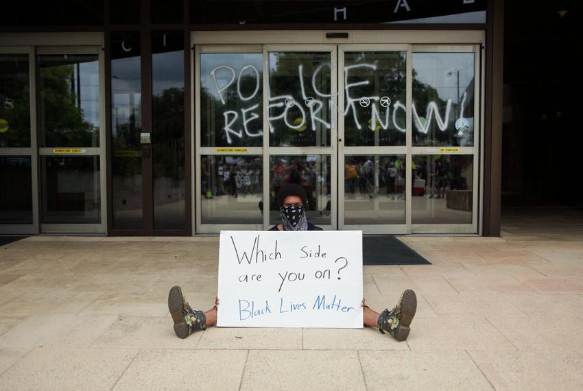 A protester sits outside an entrance to City Hall in Austin on May 31, 2020.