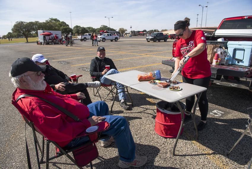 Aaron Ramsey prepares food for family and friends at their tailgate party before Texas Tech's home coming game against West …