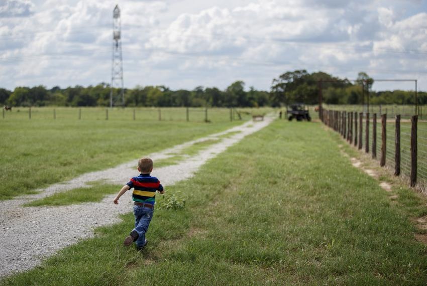 5-year-old Cainen Calhoun runs to catch up to his father Charlie on his family's land in Bedias, Texas, on Sept. 15, 2018....