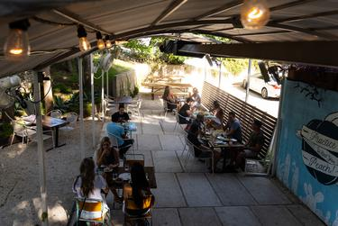 Customers sit at tables appropriately spaced for social distancing at Bar Peached in downtown Austin on Aug. 13, 2020.
