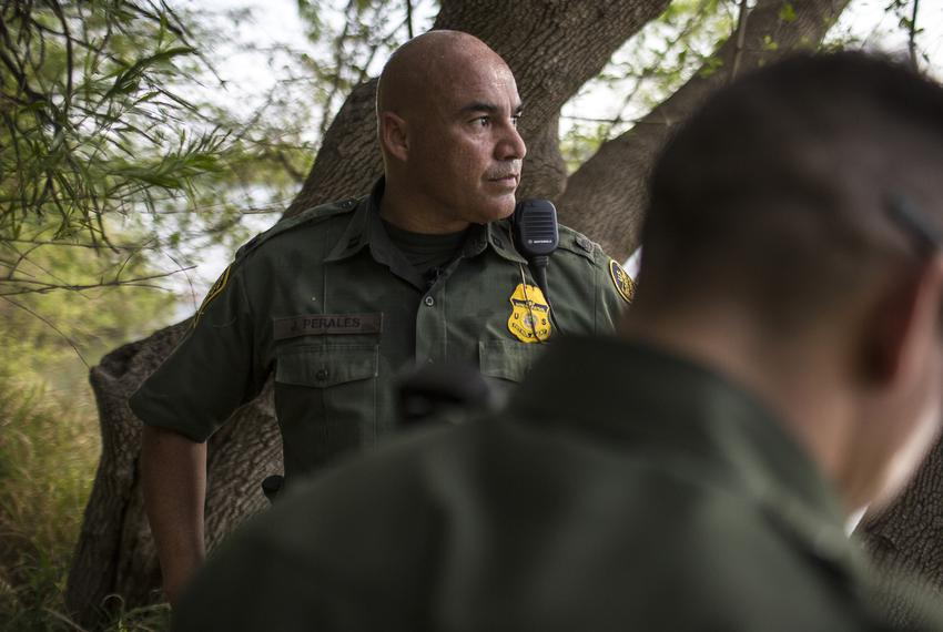 Border Patrol Agent José Perales peers out across the Rio Grande in Roma, Texas, while searching for a group of five undoc...