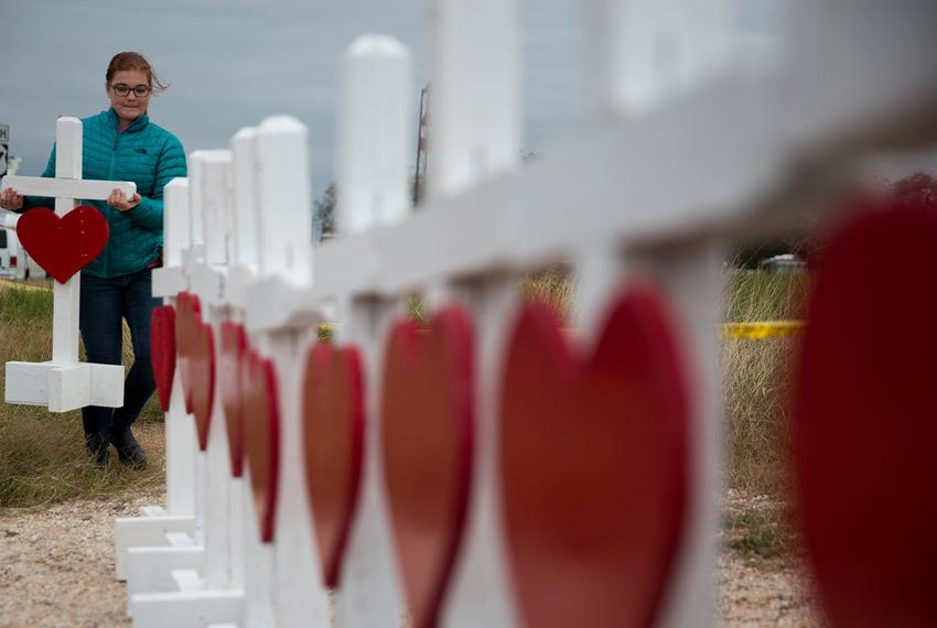 Hannah Krueger adds a cross to a memorial near the First Baptist Church in Sutherland Springs onNov. 8, 2017, three days af…