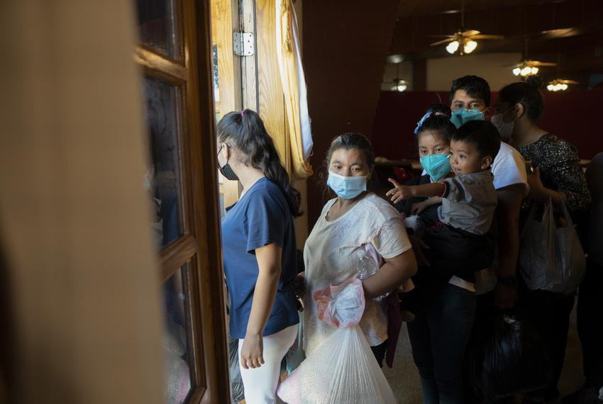 Asylum seekers exit the respite center across the street from Our Lady of Guadalupe Catholic Church in Mission on Aug. 3, 20…