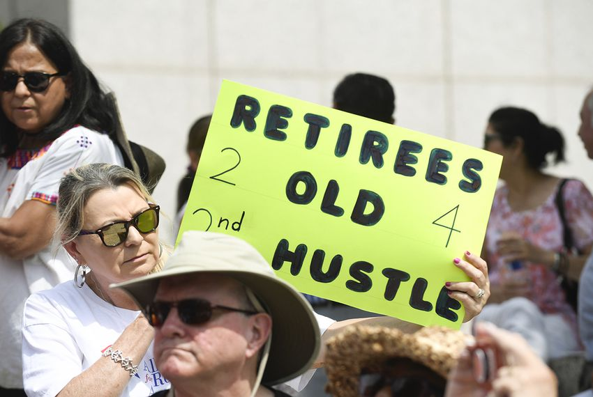Yvonne Landin, a retired teacher from Corpus Christi, holds a sign as retired teachers gather at the Teacher Retirement System (TRS) building in Austin on July 26, 2018.