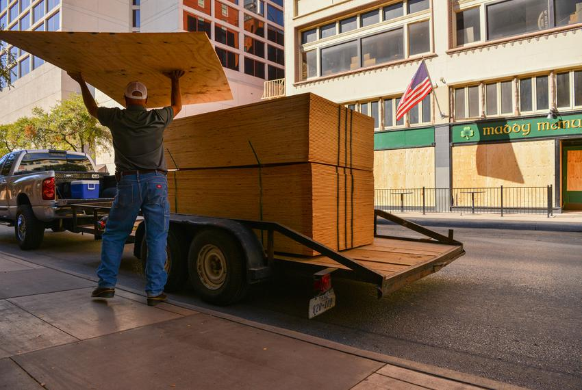 A worker unloads sheets of plywood to board up a downtown San Antonio building in the event of civil unrest as a result of t…