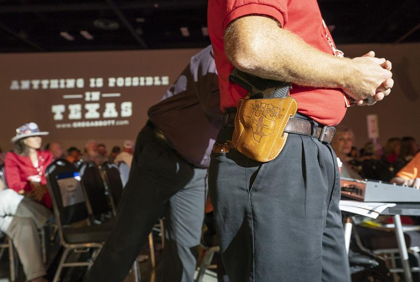 A handgun on his hip, Terry Holcomb waits to ask a question at the Republican Party of Texas convention in San Antonio on Sa…