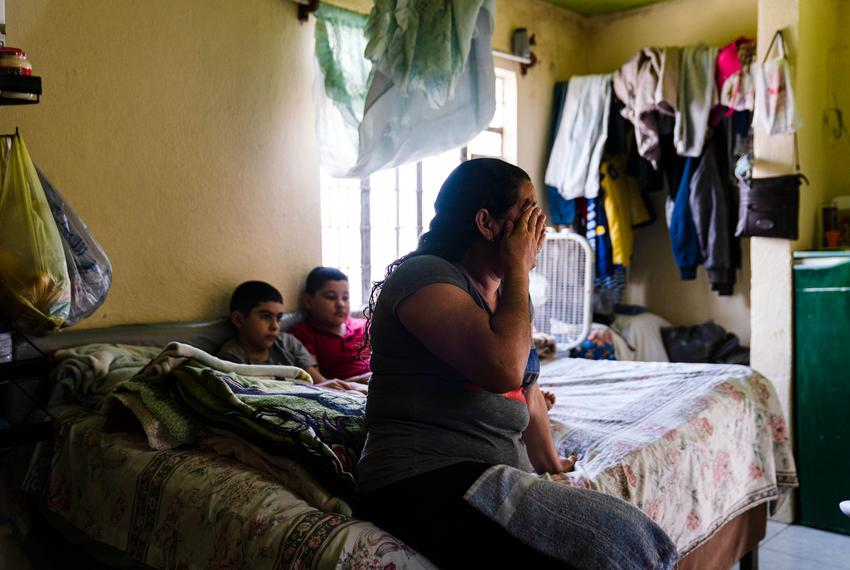 Marlen D. Cruz, 42, an asylum seeker from Honduras, cries as she shares her story of why she left her country in a bedroom t…