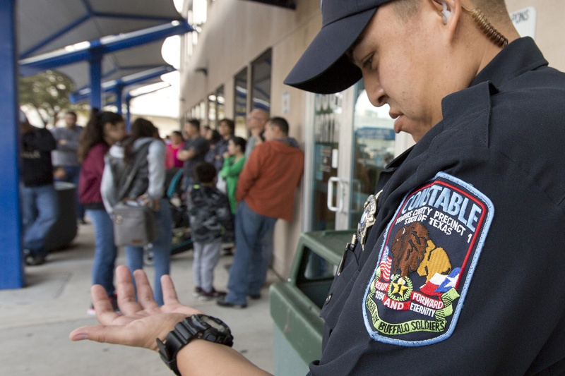 A Travis County constable checks the time outside the county passport office. The office opens at 8 a.m., but some families start lining up as early as 5 a.m.