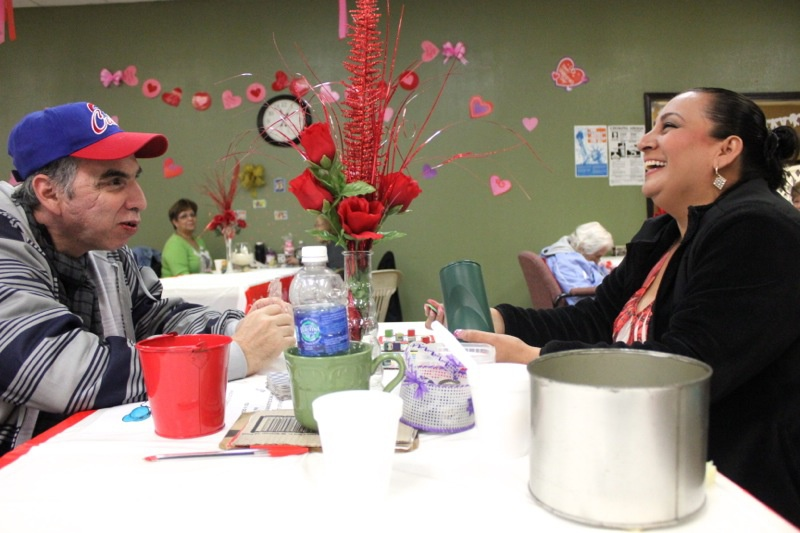 A client and a staff member play a game at an adult day care center in Mission, Texas.