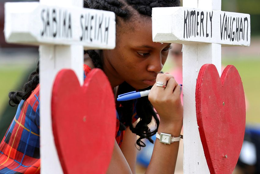 Jai Gillard, a freshman at Santa Fe High School, writes a message on a cross at a makeshift memorial left in memory of the victims killed in a shooting in Santa Fe, on May 21, 2018.