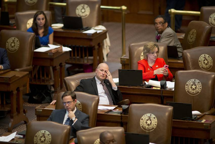 10:22 p.m. —  State Rep. Tony Tinderholt, R-Fort Worth, center, and others listen as legislation is debated.