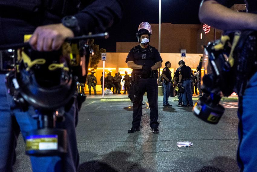 Law enforcement personnel stand guard in front of the El Paso Police Department headquarters building as protestors gathered…