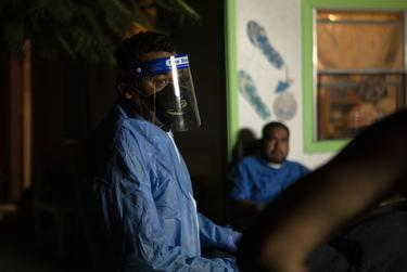 Juan Lopez speaks to the family members of a recently deceased relative. The person died of COVID-19 and Lopez reminds them of the importance of wearing masks to prevent the spread of the disease. July 17, 2020.