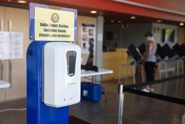 A sanitation station is positioned at the entrance of a polling site at Booker T. Washington High School in Dallas on July 14.