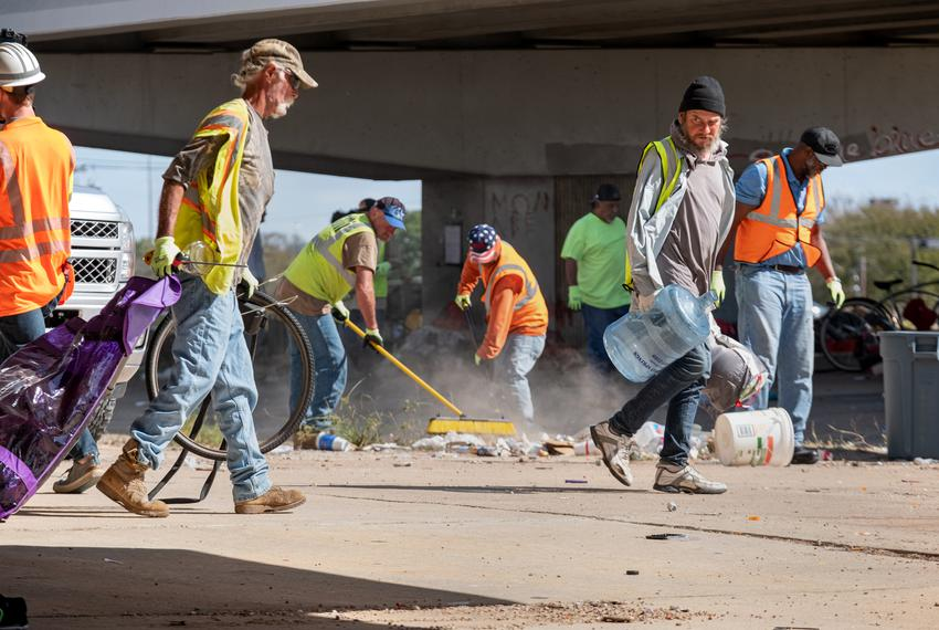 TXDOT workers remove trash and personal belongings from a homeless encampment under Highway 290 at Westgate Blvd in Austin...