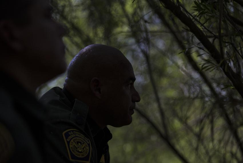 Border Patrol Agents José Perales and Isaac Villegas peer out along the Rio Grande riverbank while searching for a group of …