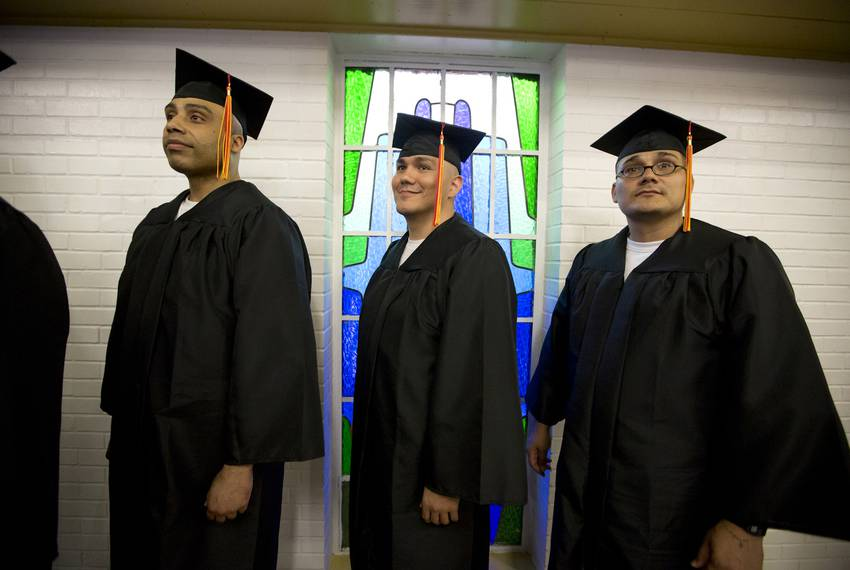 Lucien Joseph Parker, Tommy Quinones, and Raymond Ramirez, members of the prison seminary's first graduating class, line u...