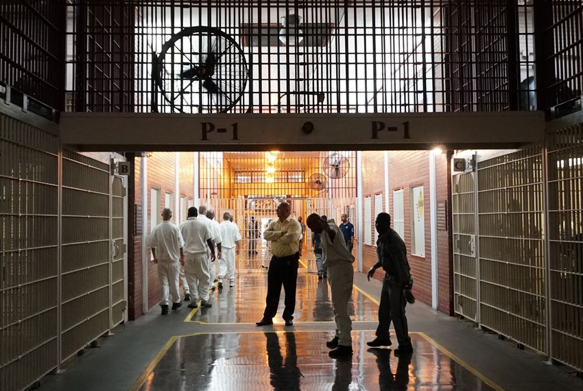 Prison staff and inmates move through the Darrington Unit's main hallway.