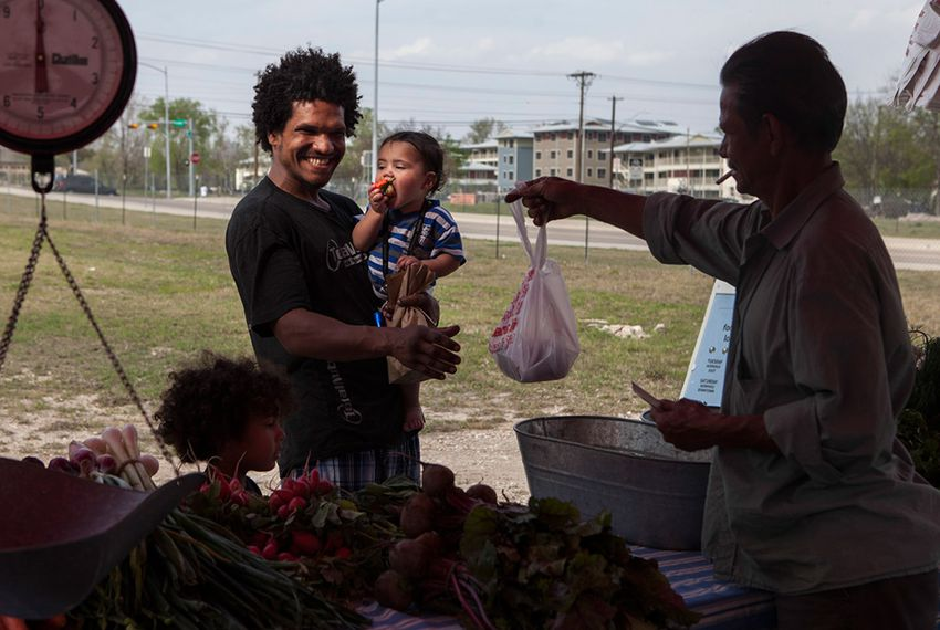 Tiger Whitehead and his children Logic and Domnick, who used SNAP and the Sustainable Food Center Farmer's Market double dollars coupons, shops at the farmer's market at 2835 East MLK Blvd. in Austin on March 19, 2013.