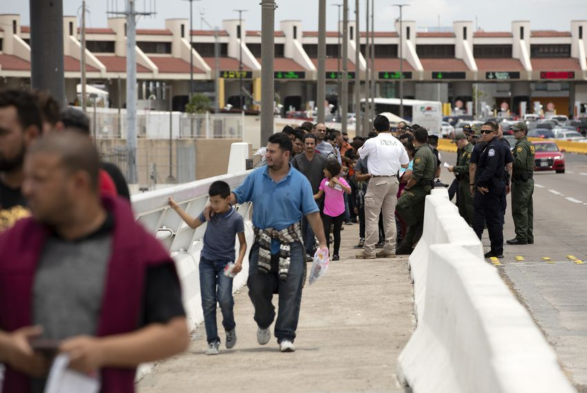 Migrants walk across an international bridge from the United States to Nuevo Laredo, Mexico, after requesting asylum in the U.S.