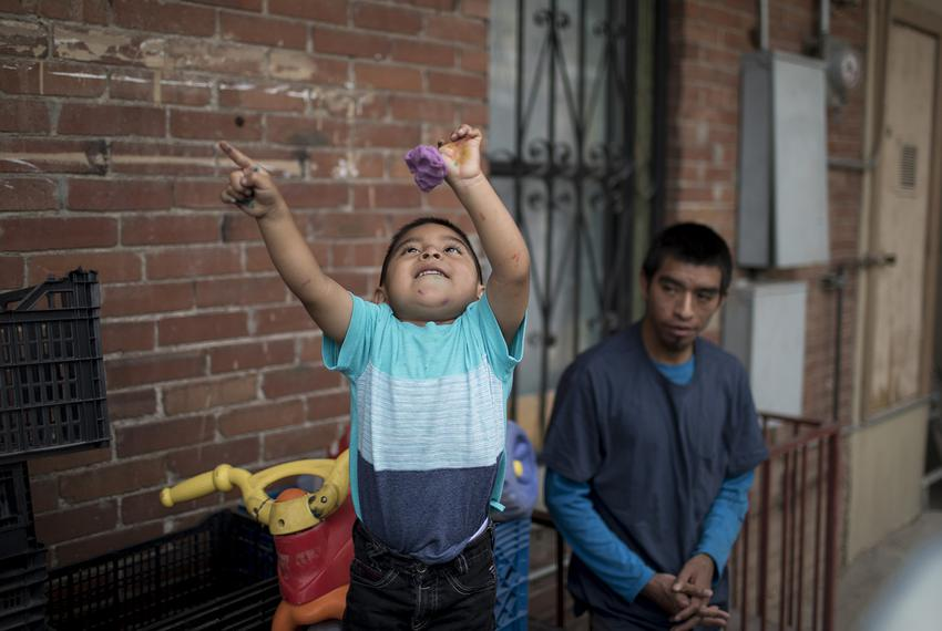 3-year-old Andres plays outside as his father Pablo Ortiz looks on outside the Annunciation House in El Paso on Wednesday, J…