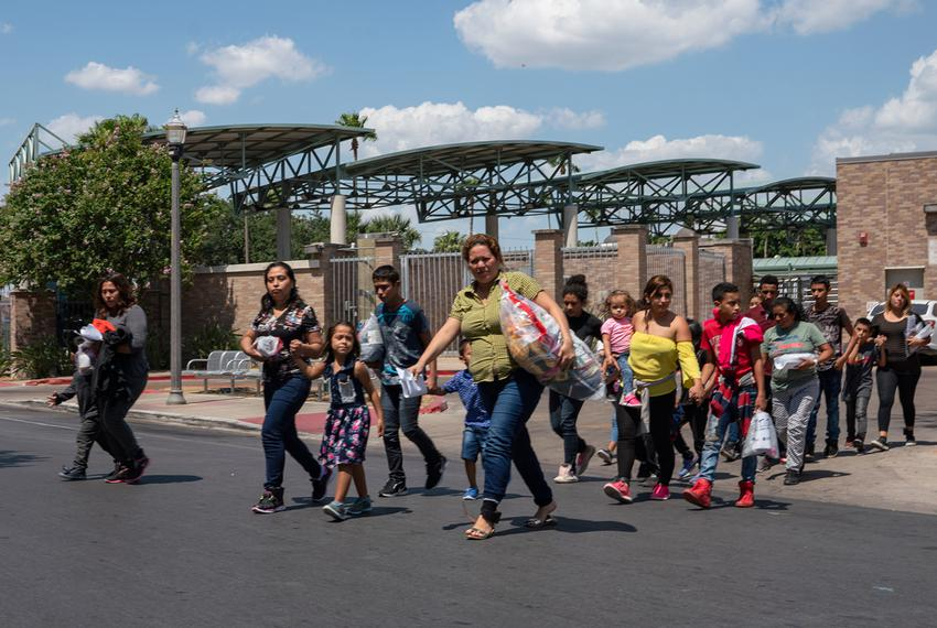 Central American asylum seekers walk to the nearby Catholic Charities Humanitarian Respite Center after being dropped off ...